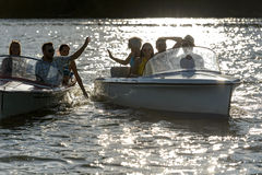 Silhouette of young friends in motorboats Stock Images