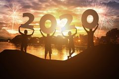 Silhouette young people hold on New year 2020 logo with sky background