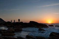 Silhouette of young people waiting for sunrise on the rock of the sea shore Stock Photos