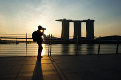 Silhouette of the young photographer at the sunrise. Royalty Free Stock Image