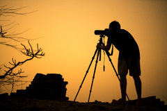 Silhouette of a young photographer during the sunset. Stock Image