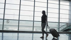 Silhouette of Young Pretty Business Woman Walking at Airport With Her Luggage While Waiting Her Queue For Registration stock video footage