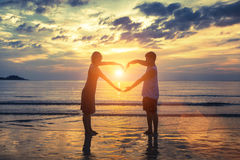Silhouette of young romantic couple during tropical vacation, holding hands in heart shape on the ocean beach during sunset.