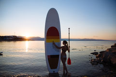 Silhouette of young sexy girl with sup surf and paddle at the ocean. Concept lifestyle, sport, love Royalty Free Stock Photos