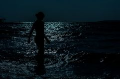 Silhouette of young, slim, woman walking in the sea under the moonlight stock image