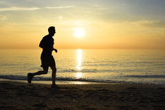 Silhouette young sport man running outdoors on beach at sunset with orange sky Royalty Free Stock Image