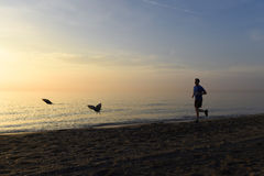 Silhouette young sport man running outdoors on beach at sunset with orange sky Royalty Free Stock Photos