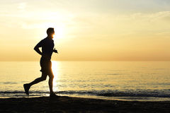 Silhouette young sport man running outdoors on beach at sunset with orange sky Stock Photography