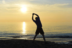 Silhouette of young sport man stretching leg after running workout outdoors on beach at sunset Stock Photo