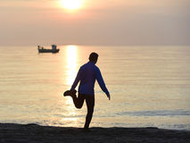 Silhouette of young sport man stretching leg after running workout outdoors on beach at sunset Stock Photos