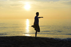 Silhouette of young sport man stretching leg after running workout outdoors on beach at sunset Royalty Free Stock Photography