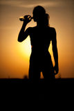 Silhouette of a young sportive woman drinking water Royalty Free Stock Images