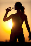 Silhouette of a young sportive woman drinking water Stock Images