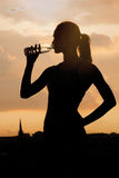 Silhouette of a young sportive woman drinking water Royalty Free Stock Photos