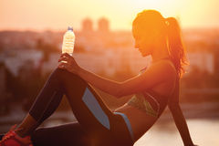 Silhouette of a young sportive woman relaxing Stock Photo
