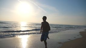 Silhouette of young sporty man running fast along coast during sunrise. Athletic boy training on beach with sea waves at. Background. Male sportsman exercising stock video