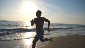 Silhouette of young sporty man running fast along coast during sunrise. Athletic boy training on sea beach. Male