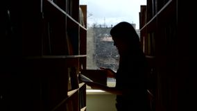 Silhouette of  young student reading a book in a. Portrait of  young student reading a book in a library, chooses a book, leaf through stock footage