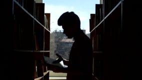 Silhouette of  young student reading a book in a. Portrait of  young student reading a book in a library, chooses a book, leaf through stock video footage