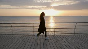 Silhouette of young stylish business woman with curly hair are walking along the wooden embankment near the sea or ocean stock video footage