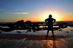 Silhouette of young teen standing at the water`s edge facing the sunset. Silhouette of young teen or tween standing on the water`s edge, looking into the sunset Royalty Free Stock Images