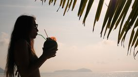 Silhouette of Young Tourist Woman Drinking Fresh Thai Coconut Water Cocktail at Tropical Beach. 4K, Slowmotion. Phuket. Thailand stock video