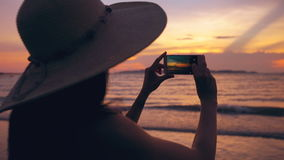 Silhouette of young tourist woman in hat taking photo with cellphone during sunset in ocean beach. Silhouette of young tourist woman in hat taking photo with stock video