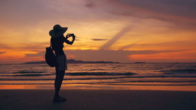 Silhouette of young tourist woman in hat taking photo with cellphone during sunset in ocean beach. Silhouette of young tourist woman in hat taking photo with stock footage
