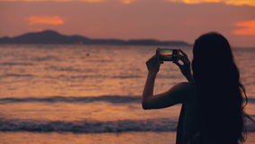 Silhouette of young tourist woman photographs ocean view with smartphone during sunset at beach. Shore stock footage