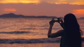 Silhouette of young tourist woman photographs ocean view with smartphone during sunset at beach. Shore Stock Photos