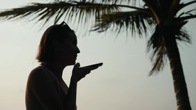 Silhouette young tourist woman use phone smartphone audio message voice recognition application ai during sunset in. Silhouette young tourist woman use phone stock video