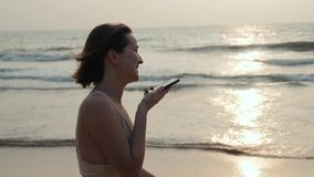 Girl young tourist woman use phone smartphone audio message voice recognition application ai during sunset in ocean. Silhouette young tourist woman use phone stock video footage