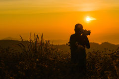 Silhouette of a young who like to travel and photographer, takin Royalty Free Stock Photo