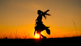 Silhouette of young witch dancing at field stock footage