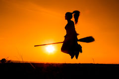 Silhouette of young witch flying on the broomstick Royalty Free Stock Image