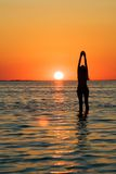 Silhouette of the young woman. With hands upwards on a bay on a sunset Stock Photo
