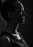 Silhouette of the young woman. Against a dark background royalty free stock image