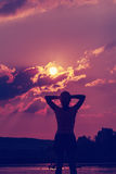 Silhouette of a young woman with arms raised in the backdrop of the setting sun Royalty Free Stock Images