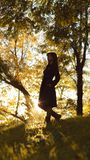 Silhouette of a young woman ascending on hill at sunset, figure girl in the autumn landscape in a dress, the concept of human and royalty free stock image