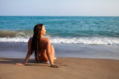 Silhouette of young woman on beach. young woman sitting in front of the seaside. Girl in bikini relaxing on the beach. Woman stock photo