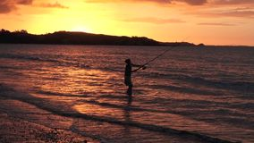 Silhouette of young woman casting rod fishing stock video footage