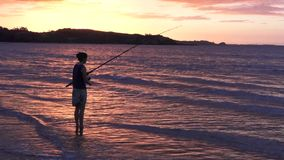 Silhouette of young woman casting rod fishing stock video