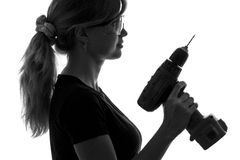 Silhouette of a young woman construction worker with a screwdriver and goggles Royalty Free Stock Photo
