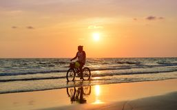 Silhouette of young woman cycling. royalty free stock image