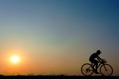 Silhouette of young woman cyclist on sunset. Sky with riding along the prairie at yellow evening horizon sea yellow sunset heaven background outdoor Stock Photography