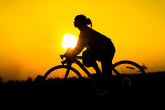 Silhouette of young woman cyclist on sunset. Sky with riding along the prairie at yellow evening horizon sea yellow sunset heaven background Outdoor Royalty Free Stock Photography