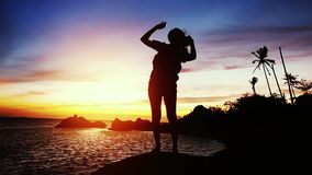 Silhouette of young woman dances at beautiful sunset stands on the rock. slow motion. 1920x1080 stock footage