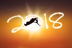 Young dancer with number 2018. Silhouette of young woman dancing with a fabric while while celebrating new year of 2018 Stock Photos