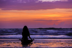 Silhouette young woman doing yoga on the beach at sunset Stock Photography