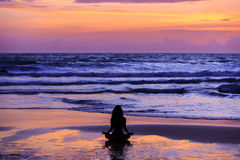 Silhouette young woman doing yoga on the beach at sunset Stock Images